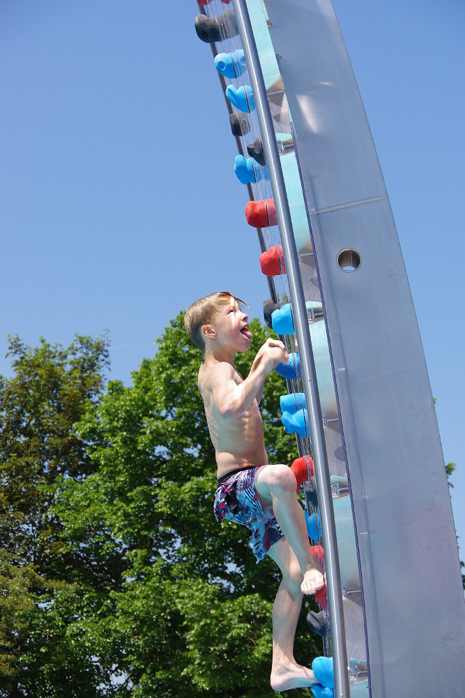 Junge an Kletterwand im Freibad