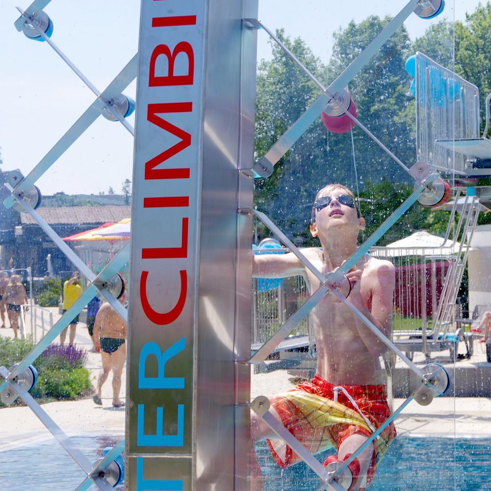 Transparente Kletterfläche einer WATERCLIMBING-Schwimmbadkletterwand